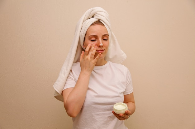 Kaukasische junge frau in einem weißen t-shirt, das gesichtscreme auf ihr gesicht setzt. beauty-konzept.