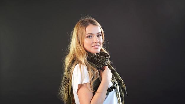 Kaukasische junge frau mit hellem haar, gekleidet in eine militäruniform, posiert vor einem dunklen hintergrund.