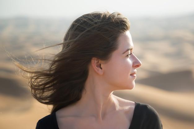 Kaukasische junge frau mit langen haaren in einem schwarzen kleid bei sonnenaufgang in der wüste
