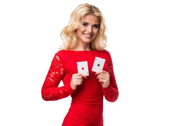 Kaukasische junge frau mit langen hellblonden haaren in der abendausstattung, die spielkarten hält. isoliert auf weißem hintergrund. poker