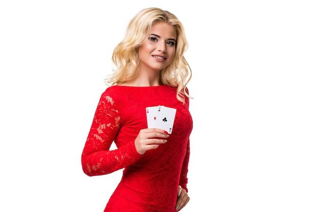Kaukasische junge frau mit langen hellblonden haaren in der abendausstattung, die spielkarten hält. isoliert. poker