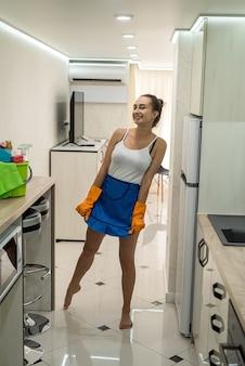 Kaukasische junge frau mit reinigungsmitteln, die ihr neues küchenzimmer säubert