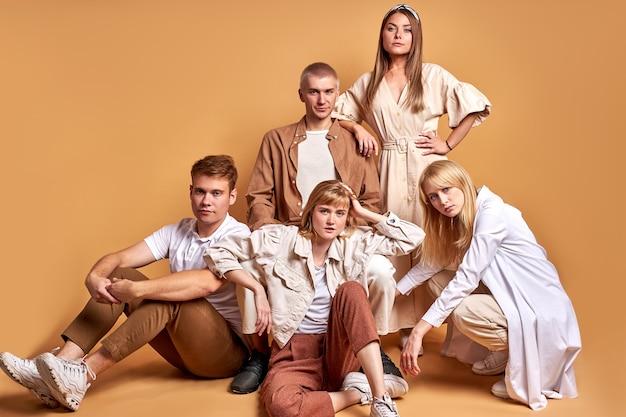 Kaukasische junge leute sitzen zusammen auf dem boden, isoliert auf braun, und tragen die gleichen stilvollen outfits
