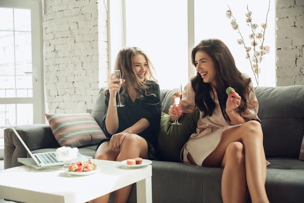 Kaukasische junge mädchen trinken champagner mit makronen.