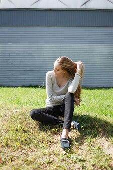Kaukasische junge magere frau mit braunem haar sitzt auf grünem rasen an der wand sitting