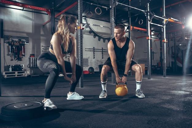 Kaukasische junge sportliche paare trainieren zusammen im fitnessstudio.