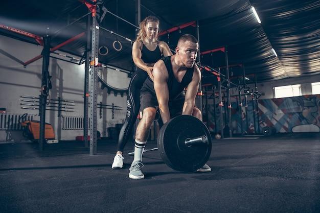 Kaukasische junge sportliche paare trainieren zusammen im fitnessstudio