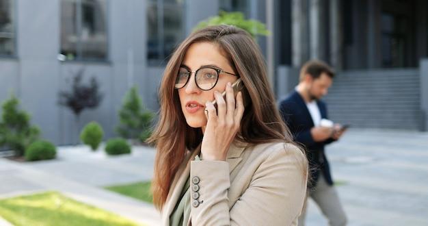 Kaukasische junge stilvolle geschäftsfrau in den gläsern, die auf handy auf der straße sprechen. schöne frau, die auf handy im freien spricht. attraktive frau in brillen, die telefonanruf haben. konversation.
