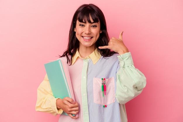 Kaukasische junge studentin, die bücher lokalisiert auf rosa wand zeigt, die eine handy-anrufgeste mit den fingern zeigt