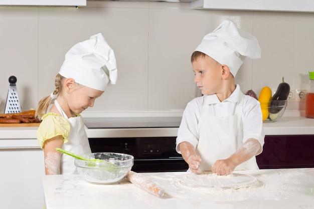 Kaukasische kinderköche spielen in der küche, während die eltern weg sind.