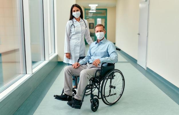 Kaukasische krankenschwester, die sich um einen reifen männlichen patienten kümmert, der in einem rollstuhl im krankenhaus sitzt. junge frau und alter mann tragen chirurgische maske, um gegen covid 19-pandemie zu schützen.
