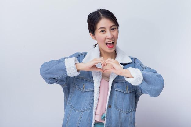 Kaukasische lächelnde frau, die ihre hand mit herzzeichen, positives glückliches junges asiatisches mädchen trägt blaues porträt der zufälligen kleidung zeigt