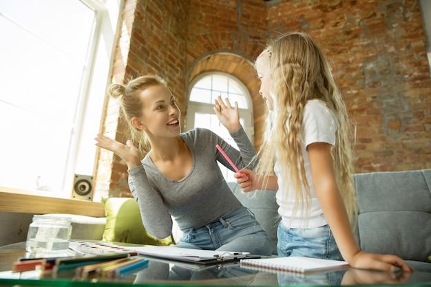 Kaukasische lehrerin und kleines mädchen oder mutter und tochter. homeschooling