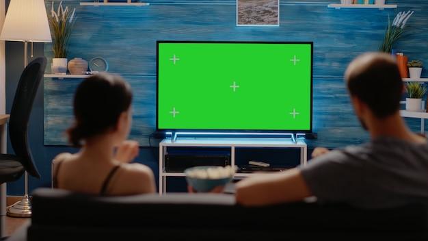 Kaukasische leute, die das greenscreen-layout im fernsehen genießen
