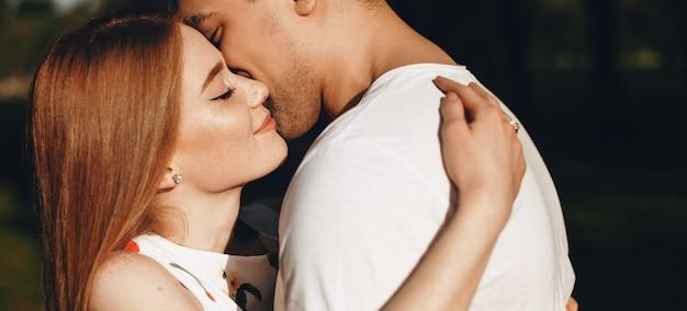 Kaukasische liebhaber in weißen kleidern, die gegen den sonnenuntergang in einem park umarmen und küssen