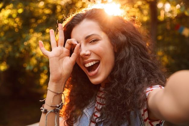 Kaukasische lockige frau, durch ok zeichen, während im freien gehen und selfie foto machen