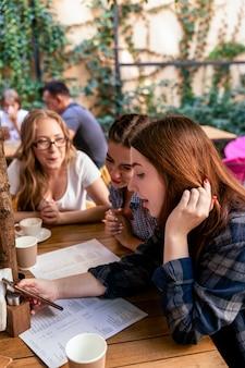 Kaukasische mädchen betrachten die vorderseite eines handys mit besten freunden im modischen café
