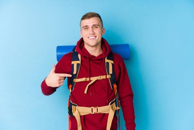 Kaukasische mannperson des jungen reisenden, die eigenhändig auf einen hemdkopienraum, stolz und überzeugt zeigt