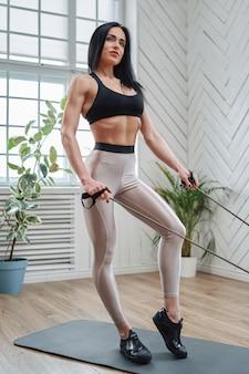 Kaukasische muskulöse und mittlere gealterte frau in sportbekleidung posiert auf der matte, die mit elastischen bändern in einem raum bleibt und trainiert.