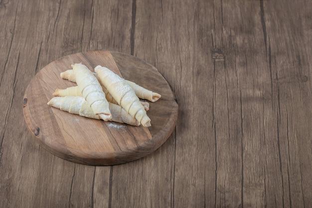 Kaukasische mutaki-kekse auf einem holzbrett mit zuckerpulver auf der oberseite.