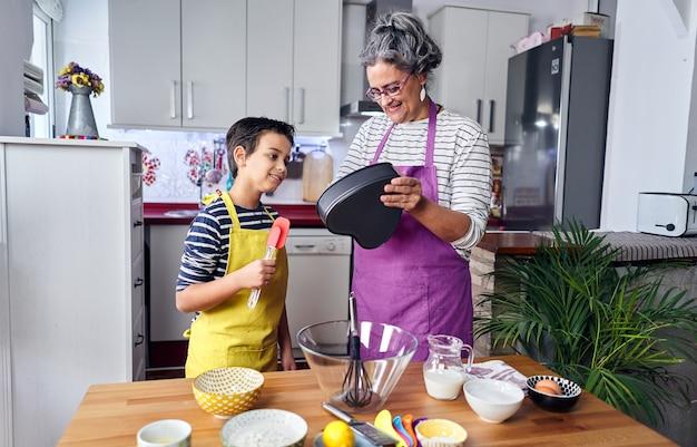 Kaukasische mutter bringt ihrem sohn bei, wie man kocht und die zutaten für einen kuchen vorbereitet