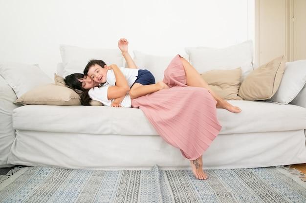 Kaukasische mutter, die auf couch liegt, kleinen sohn umarmt und mit kind spricht.