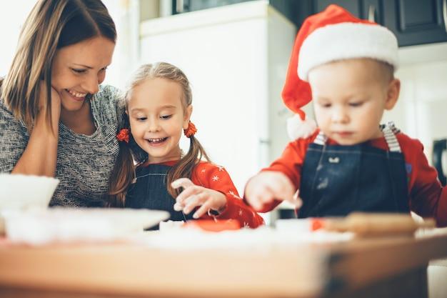 Kaukasische mutter und ihre kinder bereiten sich auf weihnachtsferien vor, tragen sant kleidung und kochen essen