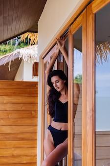 Kaukasische passform gebräunte frau, die vintage alten bikini trägt, posiert in luxushotelvilla