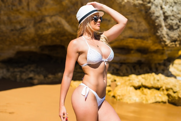 Kaukasische passform schlanke kleine frau im bikini und sonnenbrille am felsigen strand. gewichtsverlust motivation