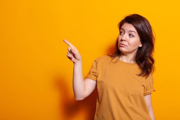 Kaukasische person, die finger auf der linken seite des studios anzeigt