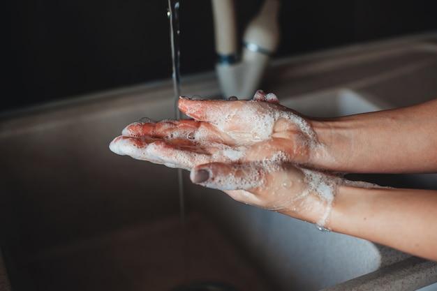 Kaukasische person, die hände mit seife wäscht
