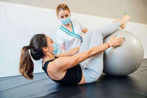 Kaukasische physiotherapeutin in einer klinik, die eine pilates-lift-behandlung mit einem therapieball gibt