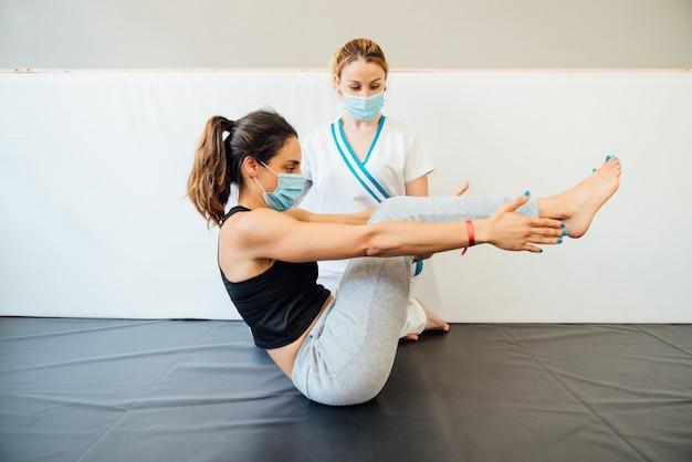 Kaukasische physiotherapeutin in einer klinik, die einem klienten mit einer gesichtsmaske aufgrund der covid-19-coronavirus-pandemie eine pilates-lift-behandlung gibt.