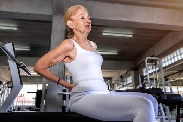 Kaukasische rückenschmerzen der älteren frau während des trainings an der eignungsturnhalle.