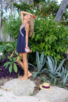 Kaukasische ruhige glückliche frau im blauen kleid hält drachenfrucht am tropischen strand