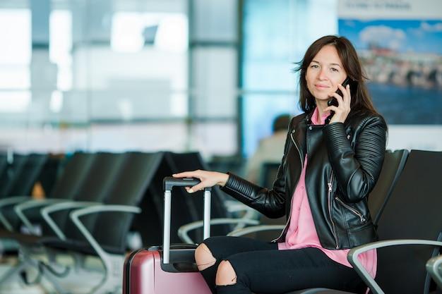 Kaukasische schauende frau, während telefonisch im warteraum spricht
