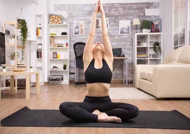 Kaukasische schöne frau, die sich zu hause in lotus-yoga-pose ausdehnt.