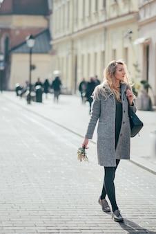 Kaukasische schöne junge blonde frau im grauen mantel und in den schwarzen strumpfhosen, die in krakauer stadtstraßen gehen.
