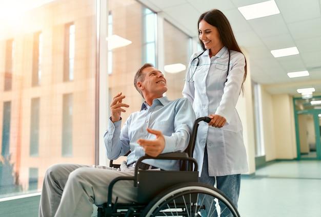 Kaukasische schöne krankenschwester, die sich um einen reifen männlichen patienten kümmert, der in einem rollstuhl am krankenhaus sitzt. die frau lächelt den älteren mann an.