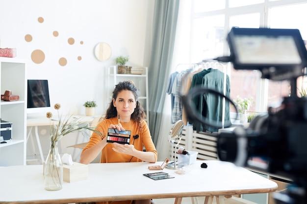 Kaukasische schönheitsbloggerin, die am tisch in ihrem zimmer sitzt und neue lippenstiftpalette vor der kamera demonstriert