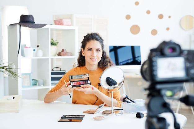 Kaukasische schönheitsbloggerin, die am tisch vor der kamera sitzt und neue lippenstiftpalettenmuster auf ihrer hand tut
