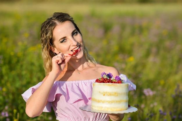 Kaukasische sommersprossige frau, die einen kuchen hält und beeren isst, die an einem sonnigen tag im freien posieren.