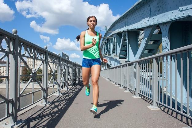 Kaukasische sportlerin, die auf der alten eisenbrücke läuft