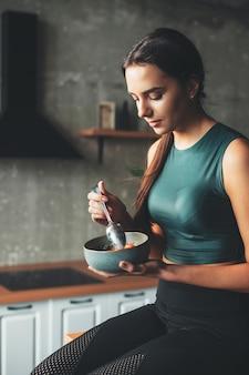 Kaukasische sportliche frau isst eine schüssel mit müsli und früchten nach der fitness-sitzung