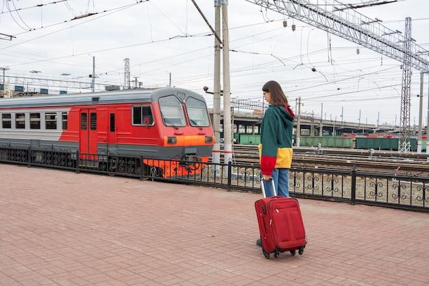 Kaukasische studentin in hellen kleidern mit einem koffer, der zum elektrischen zug am bahnhof geht. mädchen mit koffer am bahnhof. eine reise für studenten in den urlaub.
