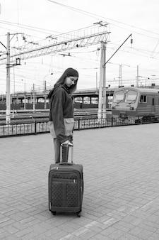 Kaukasische studentin in heller kleidung mit einem koffer, der zum elektrischen zug am bahnhof geht, schwarz und weiß. mädchen mit koffer am bahnhof. eine reise für studenten in den urlaub.