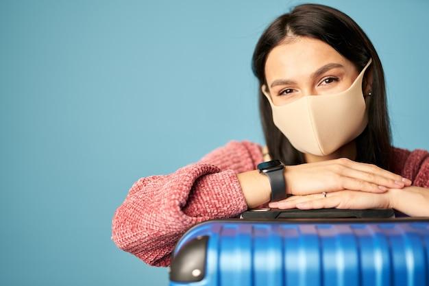 Kaukasische touristin, die eine antivirus-maske mit koffer trägt, die vor blauem hintergrund posiert. platz kopieren. konzept der reise, coronavirus
