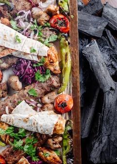Kaukasische traditionelle kebabservierplatte mit gegrillten nahrungsmitteln und kräutern.