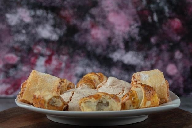 Kaukasische traditionelle kekse mit zuckerpulver oben auf weißer keramikplatte.