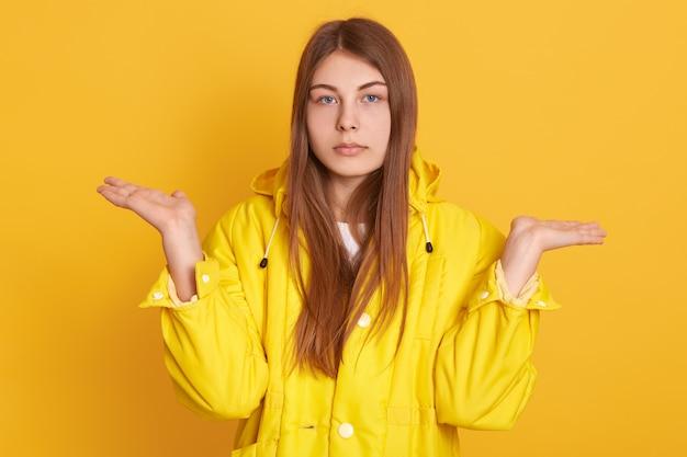 Kaukasische traurige frau, die hände beiseite spreizt, hilflose geste zeigt, dame, die jacke trägt, gegen gelbe wand posiert, hat ernsten blick, mit verärgertem ausdruck.